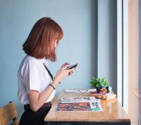Школьница смотрит в телефон