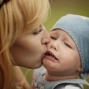 Мама целует плачущую дочь