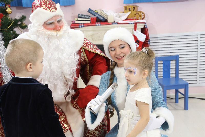 Дед Мороз и Снегурочка разговаривают в девочкой