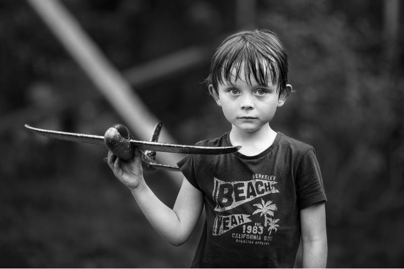 Грустный мальчик держит игрушечный самолет