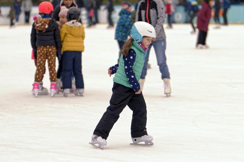 Девочка в экипировке катается на коньках