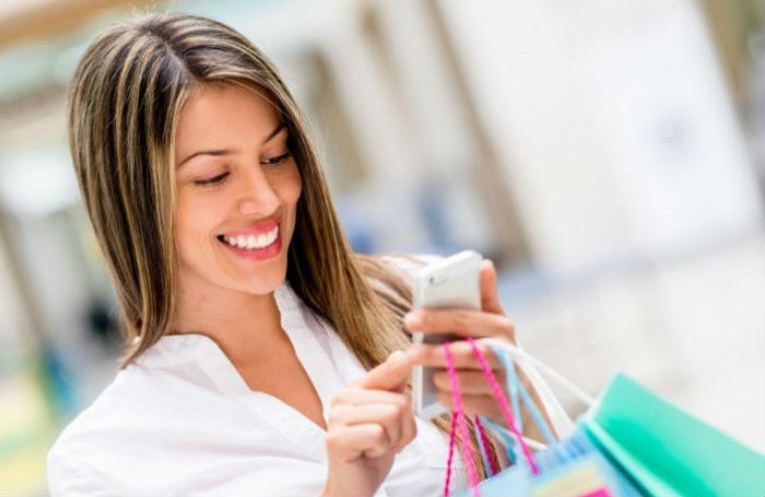 девушка с телефоном и покупками
