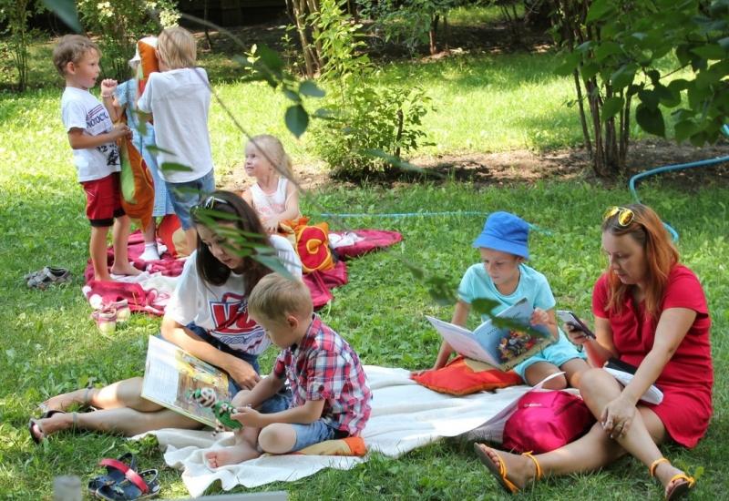 Дети и родители сидят на траве с книгами