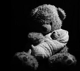 Плюшевый медведь держит закутанного плюшевого медвежонка