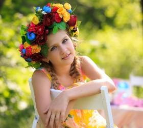 Девочка сидит в венке из цветов