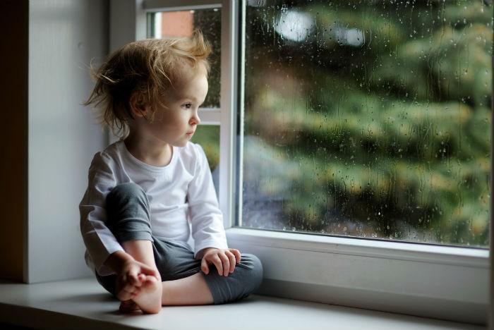 Ребенок грустит у окна
