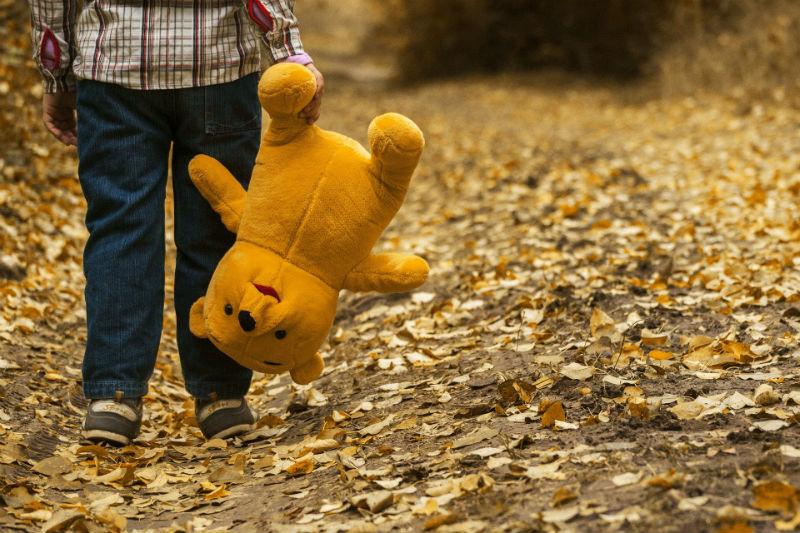 Ребенок идет по дороге и несет за ногу плюшевого медведя
