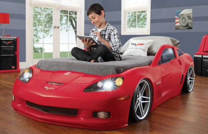 Мальчик сидит на кровати-автомобиле