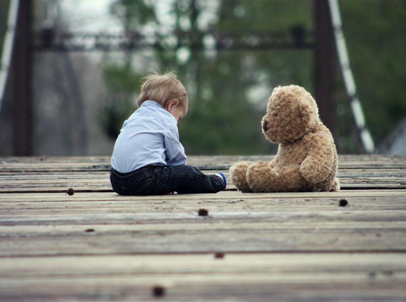Ребенок сидит на земле с плюшевым медведем