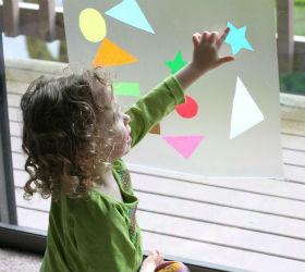 девочка играет в игру на стекле окне