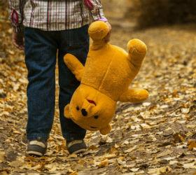 Ребенок несет за ногу плюшевого медведя