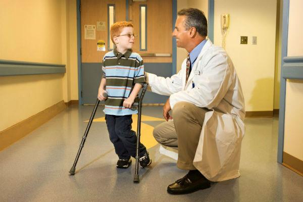Ребенок на костылях и доктор