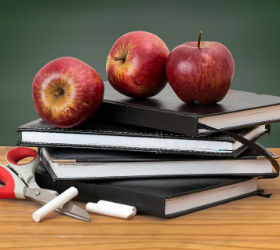 Яблоки, мел и ежедневники на столе