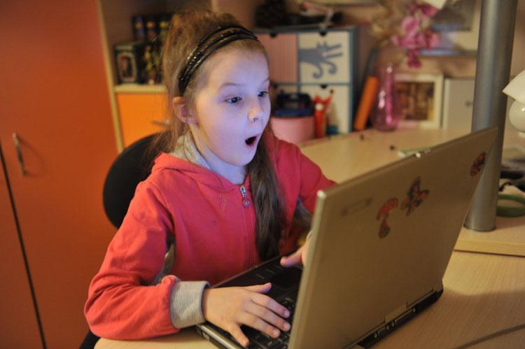девочка удивляется за ноутбуком
